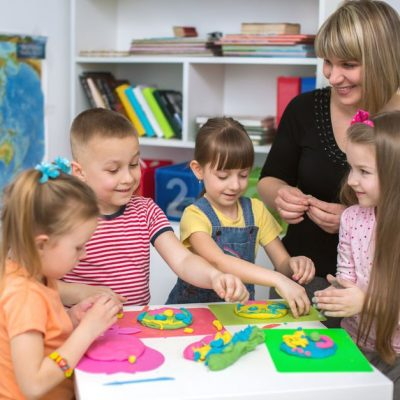 Happy children with teacher  playing with color play dough at classroom